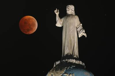 A double expousure picture shows the moon and the monument of The Savior of The World during a total lunar eclipse as seen from San Salvador, El Salvador on December 21, 2010. This eclipse takes place just hours before the December solstice, which marks the beginning of northern winter and southern summer. AFP PHOTO/ Jose CABEZAS (Photo credit should read Jose CABEZAS/AFP/Getty Images)